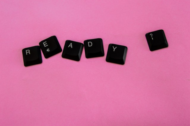 """Black keys of a computer keyboard forming the phrase """"Ready?"""" isolated on pink background. Concept of being prepared with free space."""
